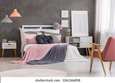 Cozy double bed with many pillows and blankets in a modern, gray and pastel teenage girl bedroom interior