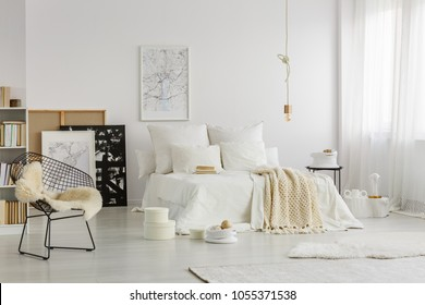 Cozy double bed with white sheets, pillows and warm beige blanket in a hipster apartment interior of an art and books lover