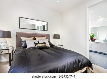 Cozy double-bed with cushions and side-tables with table lamps in the background