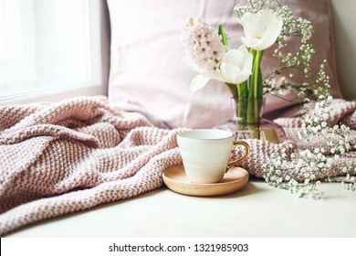 Cozy Easter, spring still life scene. Cup of coffee, pink knitted plaid and floral bouquet in vase on windowsill. Vintage feminine styled photo. Composition with tulips, hyacinth and Gypsophila flower