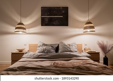 Cozy and elegant bedroom with big bed, nice bedclothes, wooden bedside tables and rattan pendant lamps with warm light