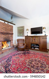 Cozy and elegant living room with a large carpet, a leather armchair and a fireplace