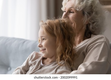 In cozy embraces of grandma. Adorable girl grandchild relax on couch in loving granny arms listen to stories wise advices. Smiling preteen girl feel emotional bonding with caring aged female custodian