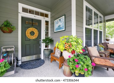 Cozy entrance porch with flower pots and seating arrangement. Northwest, USA