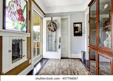 Cozy entry room in small craftsman house with decorative window and vintage cabinet with glass doors.