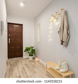 Cozy entryway with wooden floor panels and shoe bench