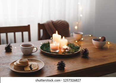 Cozy evening tea party by candlelight. Served table: cup of tea, cookies, tray, candles, pine cone, branches, led garland lights. Table setting. Christmas or New year holiday decorations. Table decor.