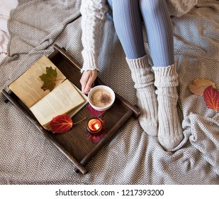 Cozy fall indoor female with woolen socks, coffee and candle, soft cozy bed blanket