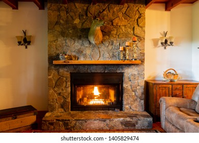 Cozy fireplace with deer head in the living room of a  mountain cabin in North Carolina.
