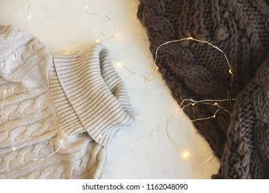 Cozy flat lay. Winter and autumn warm clothing: sweater, scarve and garland on white concrete textural background. Decorations for Christmas holidays.