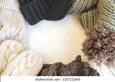 Cozy flat lay. Winter and autumn warm clothing: sweaters, scarves, gloves on white concrete textural background. Decorations for holidays