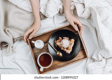 Cozy flatlay of bed, woman's hands holding wooden tray with vegan apple pie, ice cream and black tea on white sheets and blankets