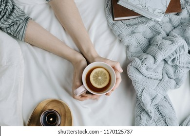 Cozy flatlay of woman's hand holding lemon tea in bed with white sheets and blanket, knitted sweater and candle