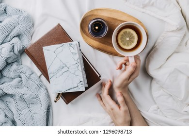 Cozy flatlay of woman's hands in bed with knitted sweater and books holding cup of lemon tea
