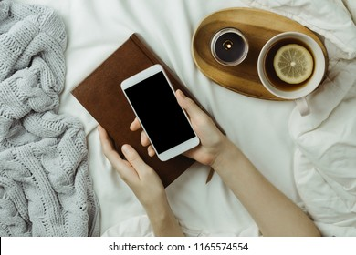 Cozy flatlay of woman's hands holding smartphone with black screen in her bed with cup of black lemon tea, candle and book
