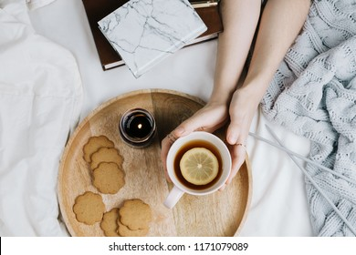 Cozy flatlay of woman's hands holding cup of lemon tea in bed with knitted sweater, candle, gingerbread cookies and books, selective focus