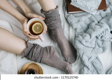 Cozy flatlay of woman's legs in warm grey stockings in bed with knitted sweater and books holding cup of lemon tea, selective focus