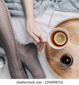 Cozy flatlay of woman's legs in warm grey stockings in bed with knitted sweater holding cup of lemon tea