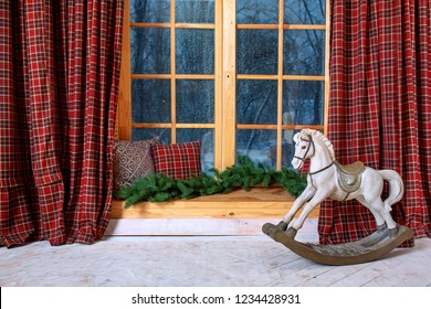 Cozy and frost winter day: christmas decoration in children room wood windowsill and hors toy.