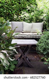 Cozy garden lounge chair with pillows, surrounded by green shrubs. Also available in horizontal.