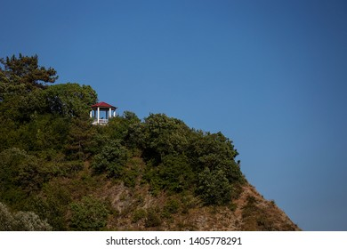 cozy gazebo is built on a cliff overgrown with green trees mountains as a landscaping area for tourists in the national Park, a view of the gazebo from the background of a clear blue sky