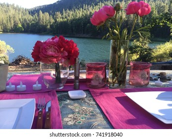 A cozy Glamping picnic table setting with white plates and pink linen napkins and flowers  with a spectacular view of Lett's Lake and the blue water, mountains and pine trees in California