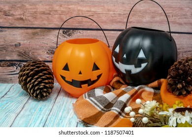 Cozy Halloween autumn concept background with pumpkin jackolantern buckets, orange plaid blanket, pine cones and flowers on wood background