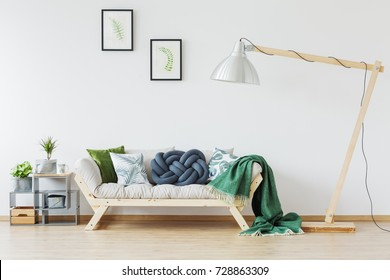 Cozy and harmonious space in living room interior with comfy wooden couch, plants, lamp and green blanket
