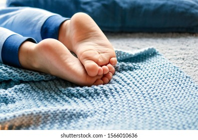 Cozy holidays at home. Close up photo of little child barefooted feet on blue knitted blanket lying on floor in pyjama. Winter season lifestyle. Leisure time. Sweet childhood. Copy space