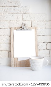 Cozy home arrangement with coffee cup and blank clipboard mockup