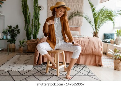 Cozy home atmosphere. Stylish woman in linen clothes sitting on chair over bed and home plants. Soft colors.