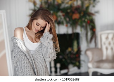 cozy home beauty portrait. sexy woman portrait. young girl in warm knitted cardigan. Portrait young beautiful brunette with long hair at home.
