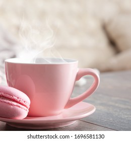 Cozy home composition. Steaming cup coffee or hot drink and macaroon  on wooden white table. Front view, copy space