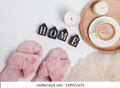 Cozy home concept. Pink fluffy feminine slippers, coffee and wooden letters arranged in a word Home, top view