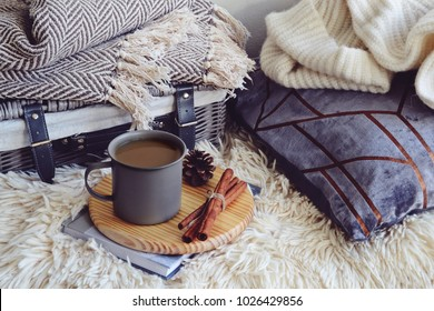 Cozy home with cup of coffee with  blanket and book. Hygge home interior