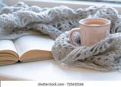Cozy home with cup of coffee and a book. Hygge style. Mug of black coffee wrapped in warm scarf on wooden board. Top view, vintage style, Still life.
