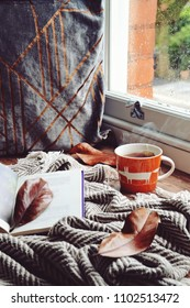 Cozy home with cup of tea with blanket and book. Hygge home interior