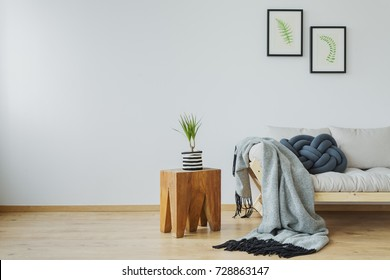 Cozy home decor with natural tree stump table, plant, posters and soft gray cotton blanket lying on the wooden beige couch