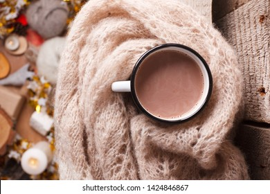 Cozy home details, winter season, hygge concept - cup of cocoa and woolen scarf on wooden, mindfullness and relax background