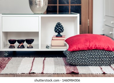 Cozy home interior decor, white nightstand with pile of books, candles in coconut shell near a multi-colored rug with decorative pillows background