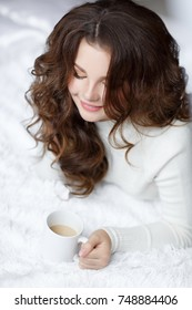 Cozy home portrait of beautiful 12 -14 years old girl drink hot chocolate and resting at winter day. Smiling teenager girl wear white knitten sweater relaxing at home interior. Winter girl portrait.