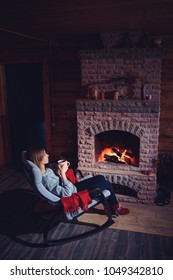 Cozy home. Pretty young woman drinking hot  beverage near the fireplace.