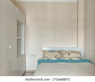 Cozy hotel room for two people. Small beige bedroom with bed and wardrobe.