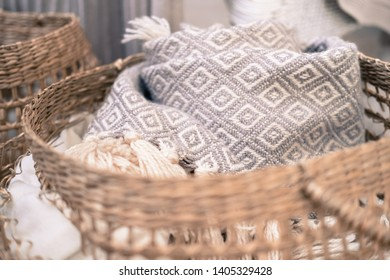 Cozy house, hugge. Knitted plaids are rolled up and placed in a wicker basket. Texture of straw, wool, fringe. Scandinavian style. The rattan chair is covered with a knitted blanket with pompons. Warm