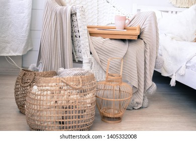 Cozy house, hugge. Knitted plaids are rolled up and placed in a wicker basket. Scandinavian style. The rattan chair is covered with a knitted blanket with pompons. A Cup of coffee is on the tray.