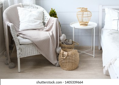 Cozy house, hugge. Knitted plaids are rolled up and placed in a wicker basket. Texture of straw, wool, fringe. Scandinavian style. The rattan chair is covered with a knitted blanket with pompons