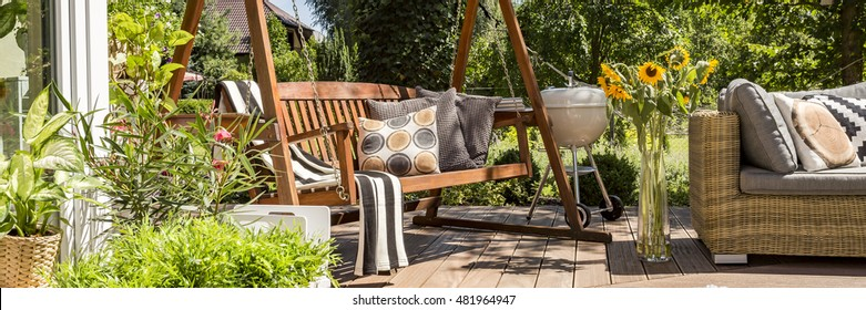 Cozy house terrace with wooden garden swing and a grill