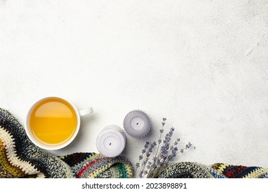 Cozy Hygge style composition with handmade woolen plaid, herbal tea, candles and dry lavender bouquet on white marble background, copy space for your design.