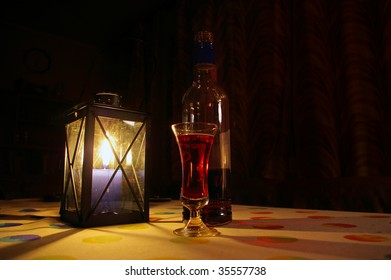 cozy indoors still-life with candle lantern and bottle and glass with red beverage