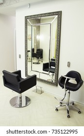 cozy interior of a beauty salon with armchairs, a mirror and furniture